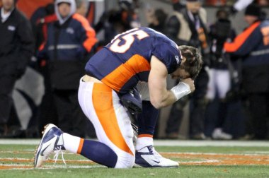 Denver Broncos quarterback Tim Tebow prays after the Broncos defeated the Pittsburgh Steelers in overtime in the NFL AFC wildcard playoff football game in Denver